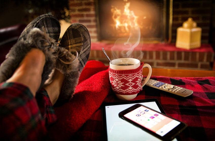 Pés sobre a mesa, com xícara de café e lareira ao fundo. Sensação de bem-estar. Imagem: Pixabay