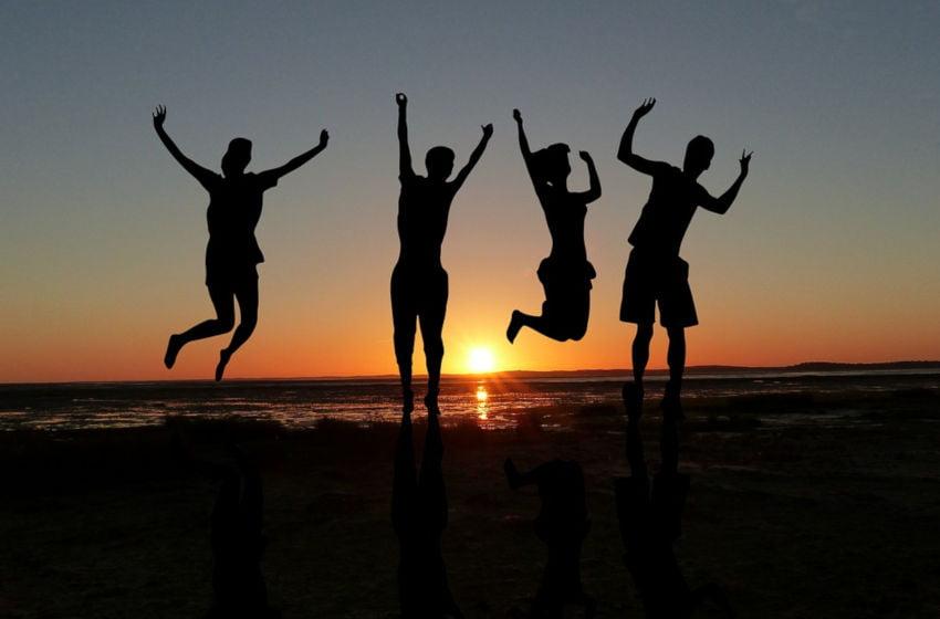 Pôr do Sol na praia, com quatro pessoas pulando. Imagem: Pixabay